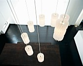 Pendant designer lamps hung in spiral above wooden table and black-varnished wooden floor