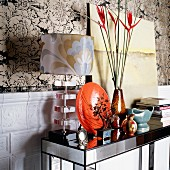 Ornaments on mirrored console table against floral wallpaper