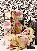 Romantic bed linen on chaise longue and floral screen against black and white wallpaper combined with simple retro lamp