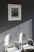 Zwei weisse Designerstühle vor grauer Wand