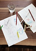 Children's drawings, crayons and full glass of water on walnut table