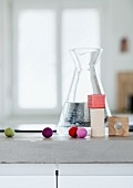 Colourful felt balls and building blocks in front of carafe of water on concrete kitchen worksurface