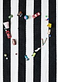 Toys arranged in heart shape on black and white striped rug