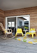 Wicker rocking chair, yellow plastic chairs and long cushion on floor of roofed wooden terrace