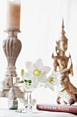 White lilies, candlestick and Oriental statue decorating table