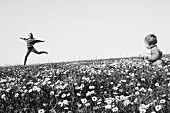 Woman skipping cheerfully though field of wildflowers and baby sitting in foreground