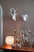 Spherical lantern next to silver Christmas decorations on antique table below china animal heads on wall