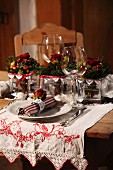 Place setting with linen napkin and wine glass in front of Christmas arrangement on embroidered runner