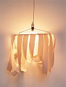 Hand-crafted sconce lamp with strips of paper attached to wire frame