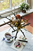 Undyed eggs in Easter nest arrangement with flowering forsythia on table
