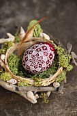 Egg artistically painted with white lace pattern in nest of twigs and moss decorated with shells