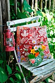 Cushion, lantern & posy in jug on old garden chair
