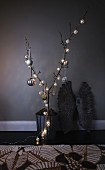 Branch in metal container decorated with string of fairy lights and silver Christmas baubles