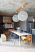 Simple white dining table in open-plan, designer dining area with elegant, purist, wooden partition shelving and concrete ceiling