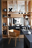 Stylish home office area with wooden, designer shell chair and elegant, fitted partition shelving