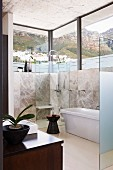 Elegant, purist bathroom with panoramic windows and view of mountains
