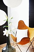 Butterfly chair with brown cover in front of black and white panel curtains; vase of white lilies in foreground