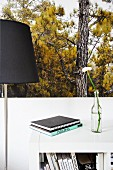 Stack of books and flower in glass bottle on white surface next to standard lamp against poster with woodland motif