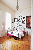 Black wrought iron bed on rustic wooden floor in white bedroom