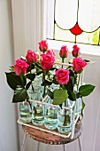 Pink roses in bottles in vintage metal bottle carrier on simple stool in front of Art Nouveau, stained-glass window