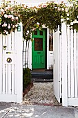 White-painted garden fence with open gate, rose climbing over trellis arch and green front door