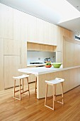 Kitchen area - fitted cupboards with seamless wooden fronts, counter with screen of same wood and bar stools with white shell seats and wooden frames