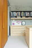 Half-height pale wooden chest of drawers below grey shelves on concrete wall and wooden sliding doors to one side in modern interior