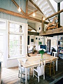 Converted industrial building with wooden gallery and white lattice windows in dining room and view into cosy, country-house-style living area