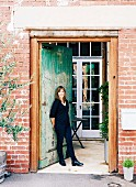 Smiling woman standing in tall, vintage front door of renovated industrial building leading into porch with white lattice door