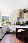 White fitted kitchen with panoramic corner window, wicker lampshade above counter and various cooking utensils arranged on stainless steel worksurface