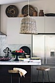 Wicker lamps above marble kitchen counter, books stacked next to fruit bowl and African basket on white wall units in background