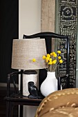 Still-life arrangement of table lamp, own ornament, antique Chinese wooden chair and ethnic wall hanging