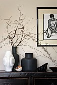 White and black vases of twigs on black Oriental sideboard below framed drawing of nude