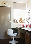 Retro swivel armchair at desk and decorative letters in window