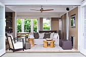 Open-plan living area with sand-coloured walls, pale, comfortable seating, scatter cushions and view of palm trees in summery garden