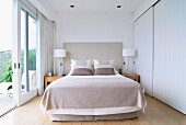 Double bed, fitted wardrobes with white sliding doors and open terrace doors in bright bedroom with view of landscape