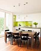 Solid wooden dining table in front of white designer kitchen with lime green splashback and access to terrace