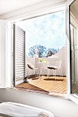 Wide open French windows in bedroom with view onto sunny, furnished terrace