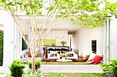 View from summery garden into open-plan modern living area