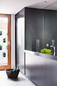 Edle grau-schwarze Einbauküche mit schwarzer Granitarbeitsplatte und Spiegel als Spritzschutz