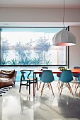 Open-plan living-dining room with panoramic window furnished with design classics