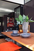 Grey crockery and black and white designer vase of leaves arranged on dining table in front of open sliding folding doors