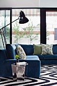 Comfortable grey-blue corner sofa, retro standard lamps and shiny side table in front of glass walls