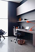 Designer work area with fitted desk, office chair, orange designer desk lamp and floor-to-ceiling window