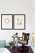 Two framed prints, antique armchair, house plants and side table next to white cupboard