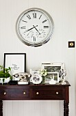 Several black and white photos in silver frames and vintage telephone on elegant console table below clock with Roman numerals on wall