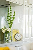White-painted fitted cupboard with mirrored niche decorated with various vases and antique alarm clock with Roman numerals