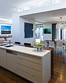 View across kitchen counter with breakfast bar into open-plan interior with ceiling zones of different heights