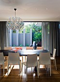 Spherical Dandelion lamp by Richard Hutten above dining table, pale plastic designer chairs and view onto terrace with blue-grey screen