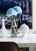 Collection of flea market vases with pastel blue hydrangeas